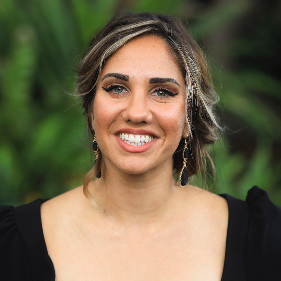 Close-up colour photograph of Kirli Saunders. Kirli is smiling, facing forward and wearing black drop earrings. The background is a blurred plant.