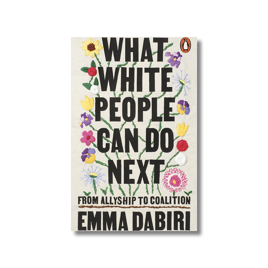 Front cover of Emma Dabiri's 'What White People Can Do Next' on a white background. The title is in a black, capitalised sans-serif font. In the background are embroidered flowers.